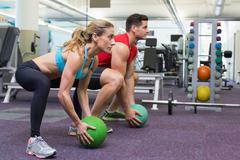 Bodybuilding man and woman lifting medicine balls doing squats Stock Photos