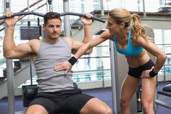 Bodybuilder using weight machine for arms with encouraging trainer - stock photo