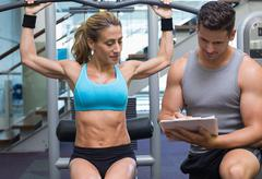 Female bodybuilder using weight machine for arms with trainer taking notes - stock photo