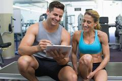 Stock Photo of Female bodybuilder sitting with personal trainer talking