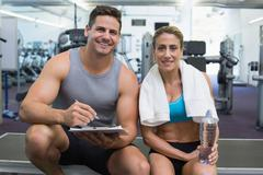 Female bodybuilder sitting with personal trainer smiling at camera - stock photo