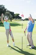 Cheering golfing couple on the eighteenth hole - stock photo