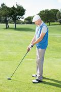 Concentrating golfer lining up his shot - stock photo