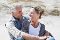 Attractive couple smiling at each other on the beach - stock photo