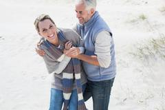 Attractive couple messing about on the beach Stock Photos