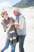 Attractive couple messing about on the beach - stock photo