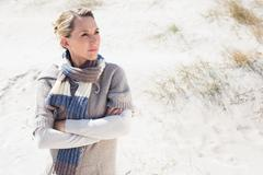 Attractive blonde standing on the beach in woolen scarf Stock Photos