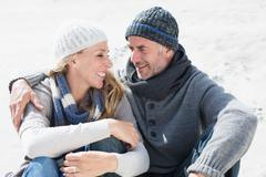 Stock Photo of Attractive couple smiling at each other on the beach in warm clothing