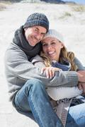 Stock Photo of Attractive couple smiling at camera on the beach in warm clothing