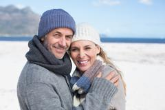 Attractive couple smiling at camera on the beach in warm clothing - stock photo