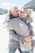 Carefree couple hugging on the beach in warm clothing - stock photo