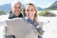 Carefree couple standing on the beach in warm clothing - stock photo