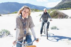 Carefree couple going on a bike ride on the beach - stock photo