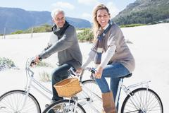 Carefree couple going on a bike ride on the beach smiling at camera - stock photo