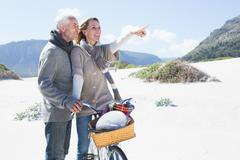Carefree couple going on a bike ride and picnic on the beach - stock photo