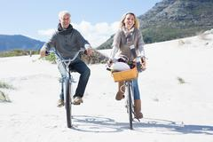 Carefree couple going for a bike ride and picnic on the beach - stock photo