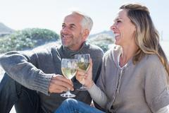 Stock Photo of Couple enjoying white wine on picnic at the beach