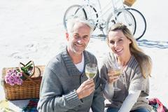 Stock Photo of Couple enjoying white wine on picnic at the beach smiling at camera