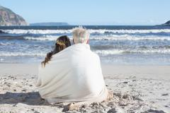 Couple sitting on the beach under blanket looking out to sea Stock Photos