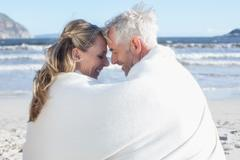 Couple sitting on the beach under blanket smiling at each other Stock Photos
