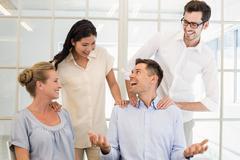 Casual business team congratulating colleague Stock Photos
