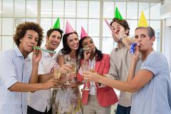 Casual business team celebrating with champagne and party horns - stock photo