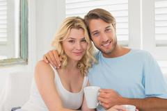 Couple having coffee on the couch smiling at camera - stock photo