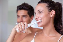 Stock Photo of Attractive couple brushing their teeth in the morning