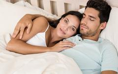 Attractive couple lying in bed smile at camera - stock photo