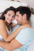 Attractive couple cuddling on bed Stock Photos