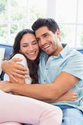 Attractive couple cuddling on the couch Stock Photos