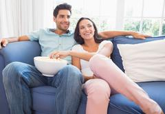 Stock Photo of Attractive couple watching tv on the couch
