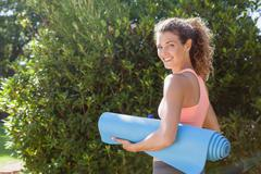 Fit woman holding exercise mat in the park Kuvituskuvat