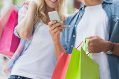 Cute young couple on shopping trip looking at smartphone Stock Photos