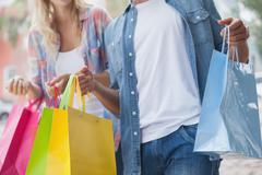 Stock Photo of Cute young couple holding shopping bags