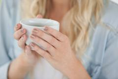 Cute blonde holding white mug Stock Photos