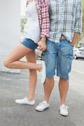 Couple in check shirts and denim holding hands - stock photo