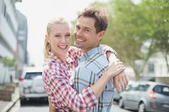 Couple in check shirts and denim hugging each other - stock photo