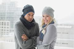 Cute couple in warm clothing smiling at camera - stock photo