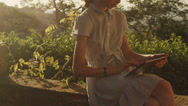 Girl is using Tablet PC in Nature at Sunset Time Stock Footage