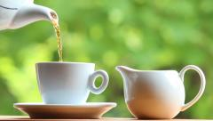 pouring tea from tea pot into a tea cup - stock footage