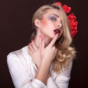 beautiful woman with flowers in head and finger on lips - stock photo