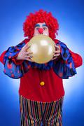 Clown with a ballon in hands on blue background Stock Photos