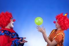 clown couple playing with ballon on blue background - stock photo