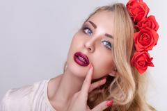 Gorgeous woman with flowers in head on grey background Stock Photos
