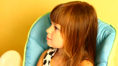 Baby girl sing and dance sit on high chair Stock Footage