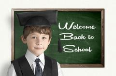 Cheerful little boy on blackboard. Looking at camera Stock Illustration