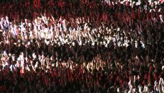 crowd of spectators on the stadium waving hands and applauding in the spotlight - stock footage