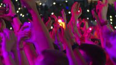 Crowd of fans waving hands and shining lights during a rock concert Stock Footage