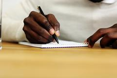 closeup portrait of a male hand writing on a paper - stock photo